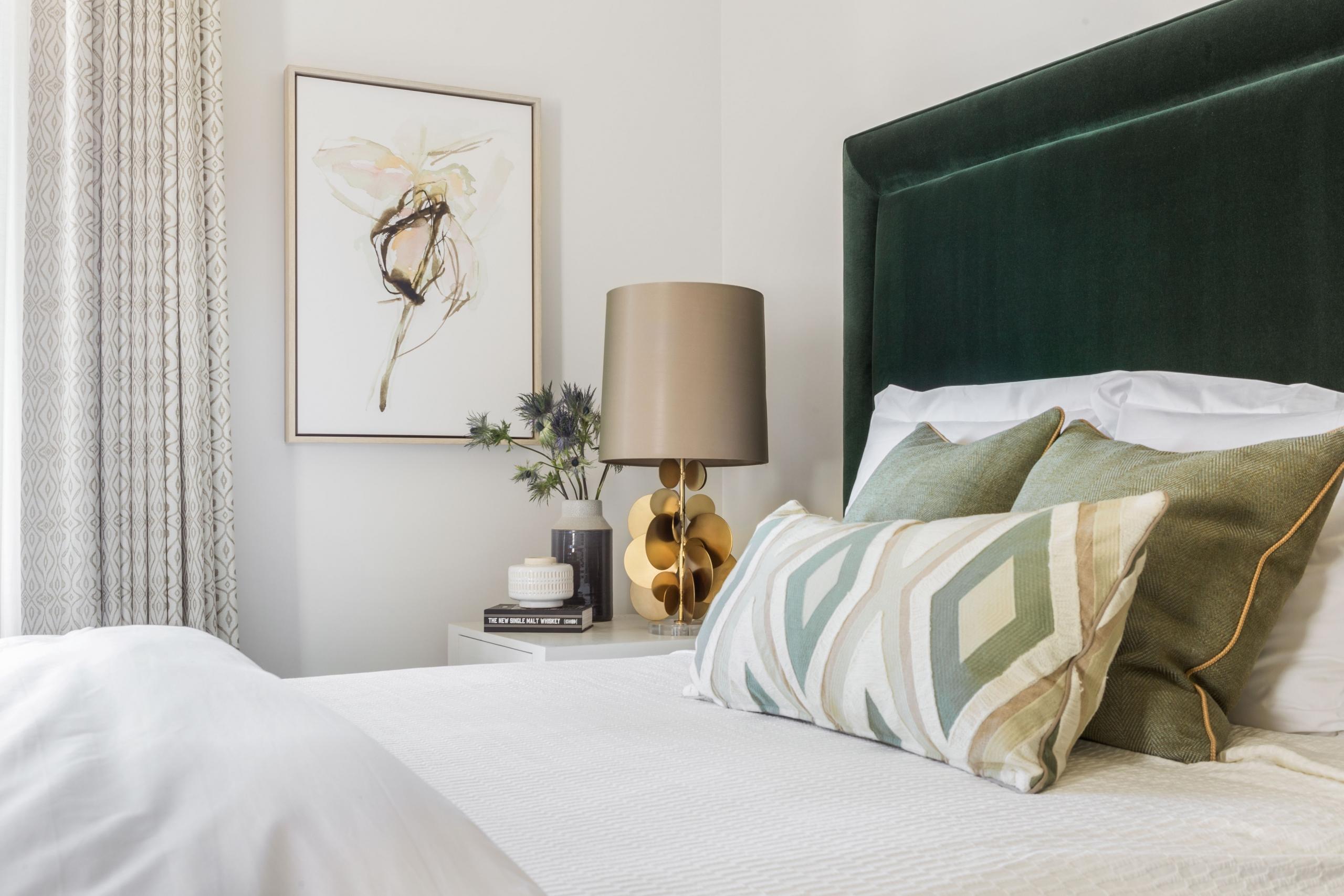 Green neutral velvet upholstered lamp on a nightstand