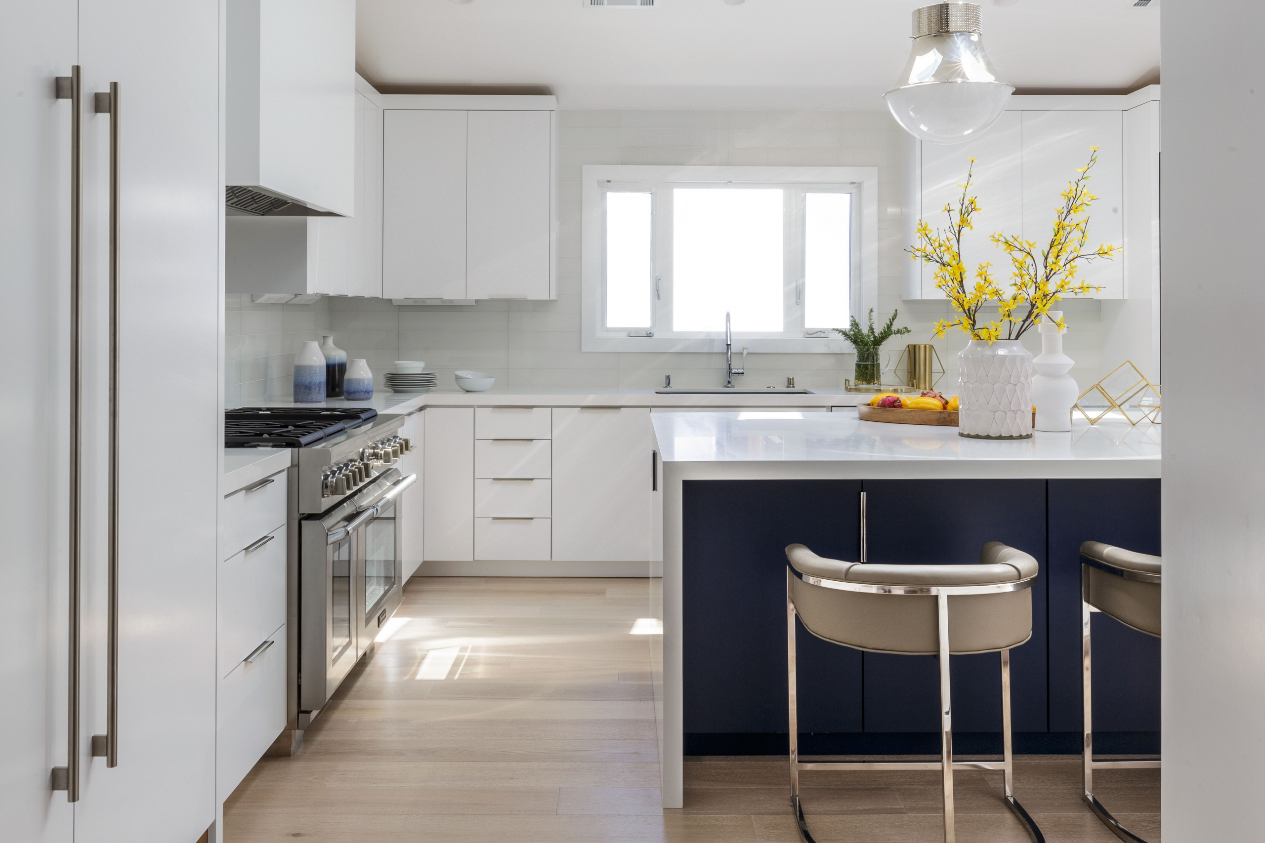 Kitchen with white island and barstools